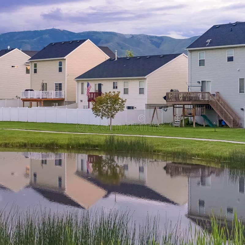 Étang brillant et voie de place parmi un terrain herbeux devant des maisons avec des balcons images stock