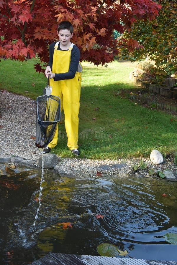 Étang de jardin de nettoyage de garçon photo libre de droits