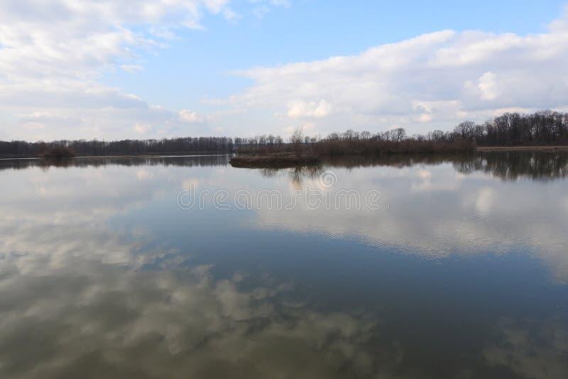 Étang et son eau paisible avec le printemps 2017 de cloudscape images stock