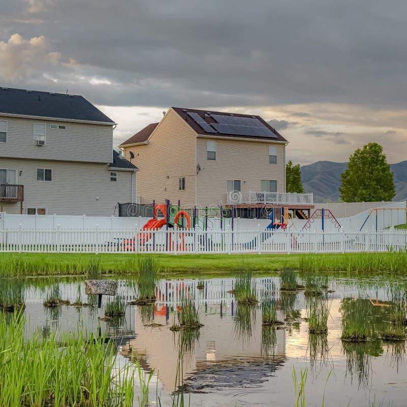 Étang herbeux brillant de place avec la réflexion des maisons ciel nuageux et barrière de terrain de jeu photo stock