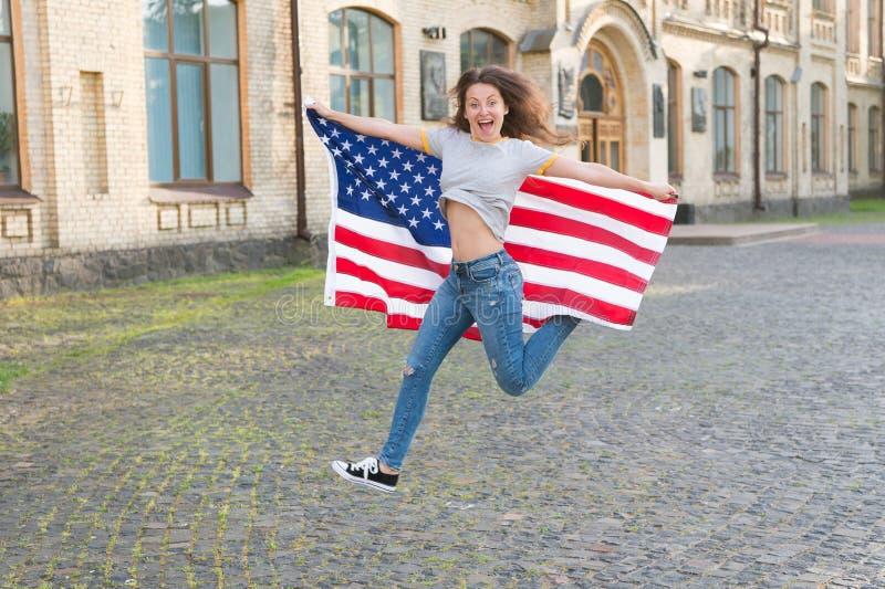 Étant la vie libre et vivante entièrement Sauter heureux de fille libre avec le drapeau américain extérieur Femme sensuelle céléb photo stock