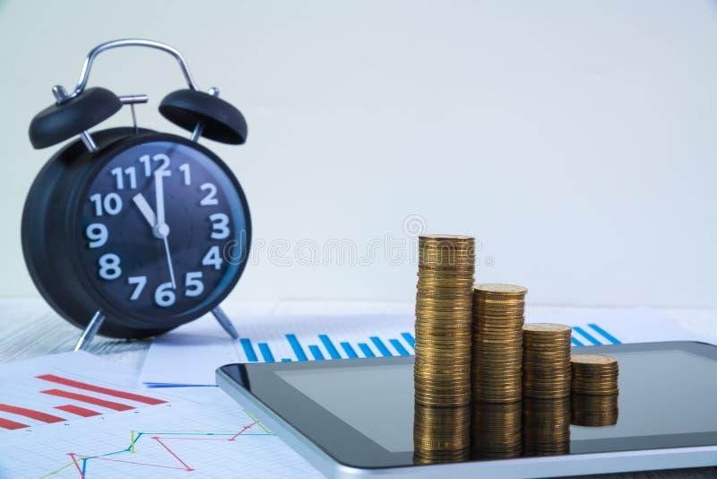 Étape des piles et du réveil de pièces de monnaie avec la tablette et le fi photos stock