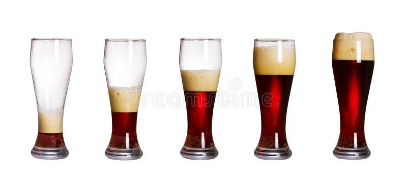 Étapes du verre remplissant de bière, d'isolement sur le fond blanc Ensemble de verres de bière foncée froide avec la mousse photographie stock libre de droits