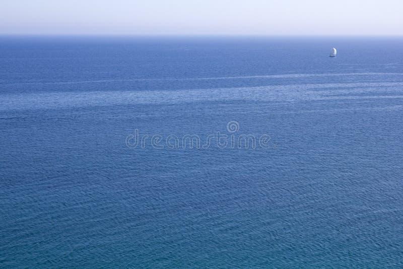 Étendue de l'eau bleue de la mer avec un voilier blanc à l'horizon photographie stock libre de droits