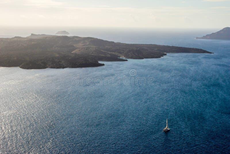 Étendues bleues de la mer Égée avec un bateau et un volcan Vue de Santorini photo stock