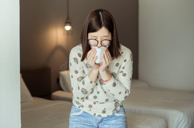 Éternuement asiatique de femme parce que pollution dans la chambre à coucher, jeune allergie obtenue femelle de nez photographie stock