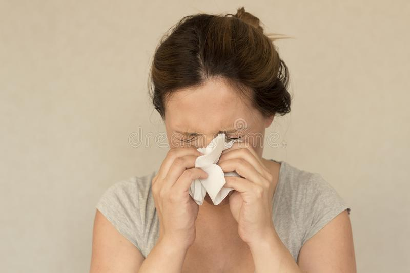 Éternuements de femme sur le fond gris concept d'allergie ou de grippe photo libre de droits