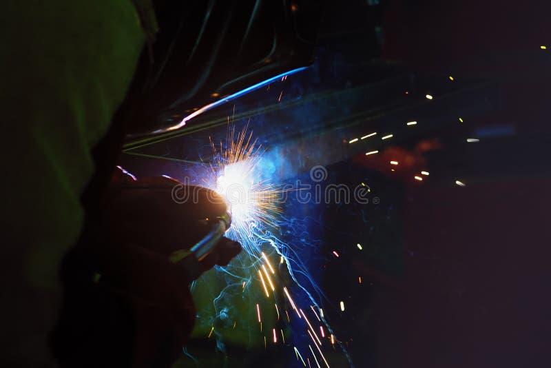 Étincelles pendant la soudure au processus de fabrication dans la soudure semi-automatique du métal en gaz protecteurs d'argon photographie stock libre de droits