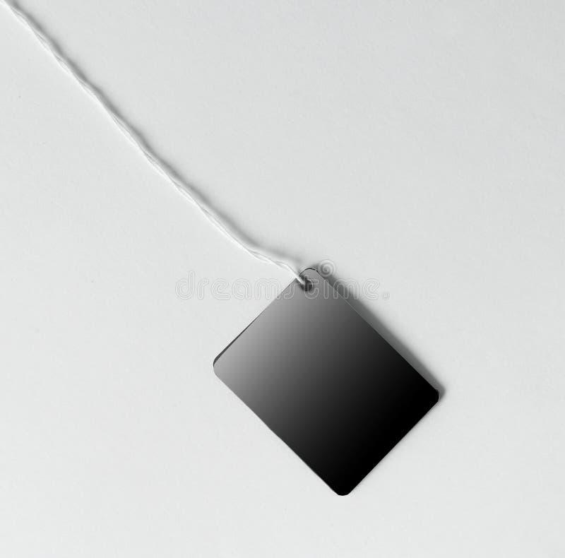 Étiquette blanc attachée avec la chaîne de caractères brune Photo avec l'espace de copie image libre de droits