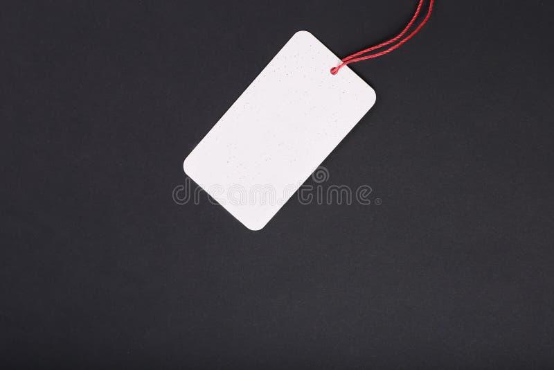 Étiquette décorative de carton de blanc avec le lien rouge de ficelle sur le fond noir images stock