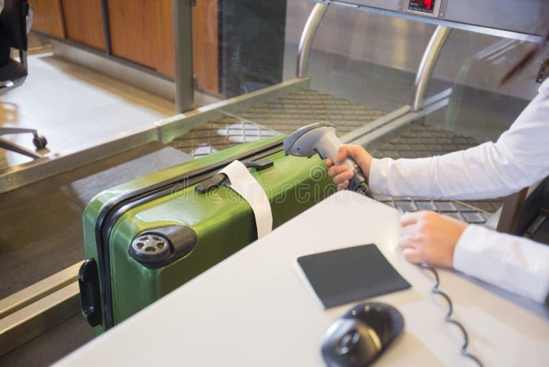 Étiquette de balayage de femme sur des bagages à l'enregistrement d'aéroport images stock