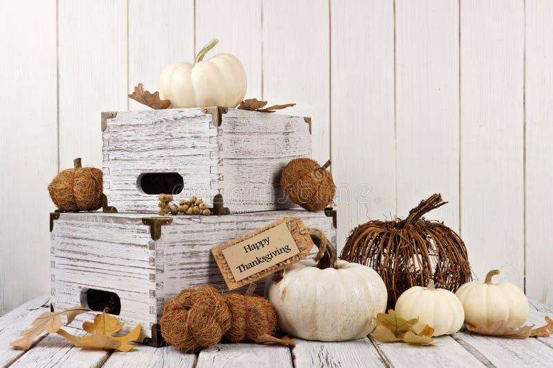 Étiquette heureuse de thanksgiving avec le décor contre le bois blanc photos stock