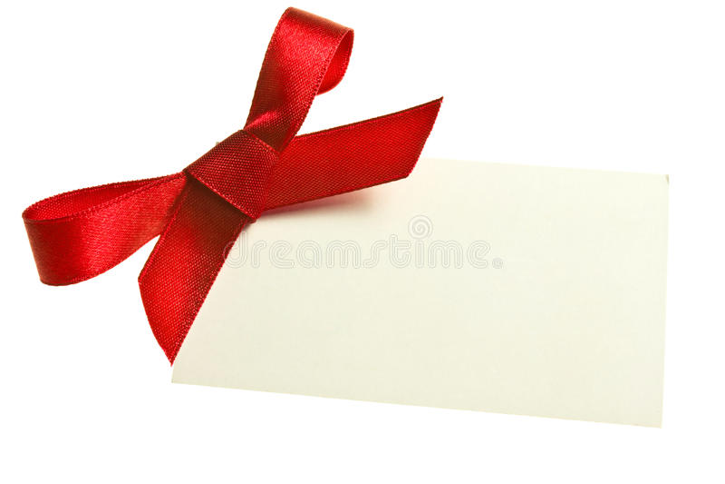 Étiquette vide de cadeau attachée avec un arc de ruban rouge de satin. D'isolement sur le blanc, avec l'ombre molle photos libres de droits
