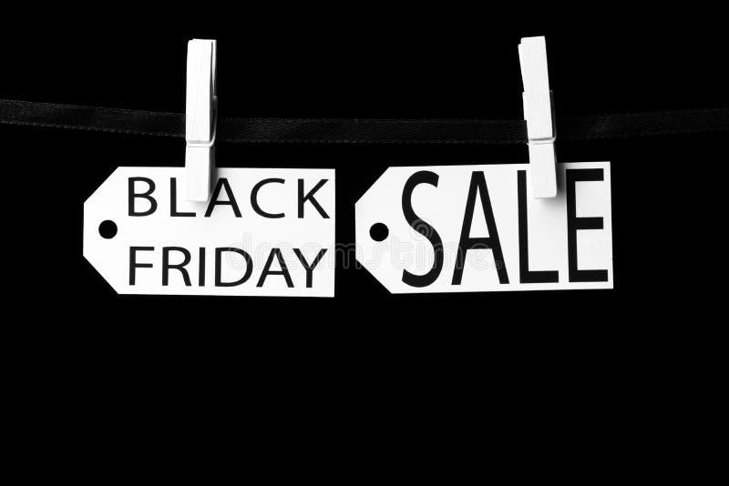 Étiquettes de vente de Black Friday attachées aux pinces à linge noires d'un ruban photo libre de droits