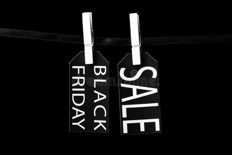 Étiquettes de vente de Black Friday attachées aux pinces à linge noires d'un ruban photo stock