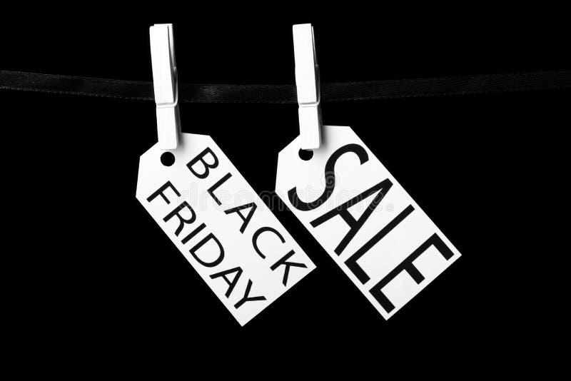 Étiquettes de vente de Black Friday attachées aux pinces à linge noires d'un ruban image libre de droits