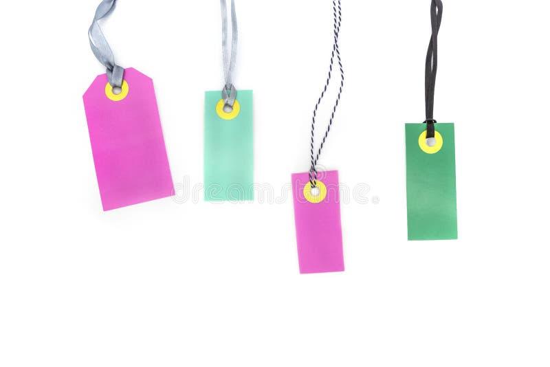 Étiquettes multicolores vides de labels faites de notes de carton ou de prix de rose et de couleur verte d'isolement sur le fond  photo stock