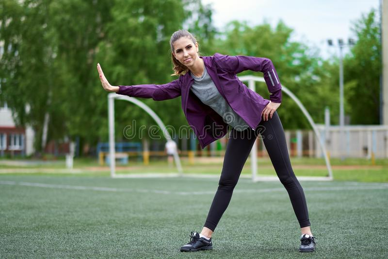 Étirage de femme Jeune séance d'entraînement femelle avant stage de formation de forme physique sur un terrain de football images libres de droits