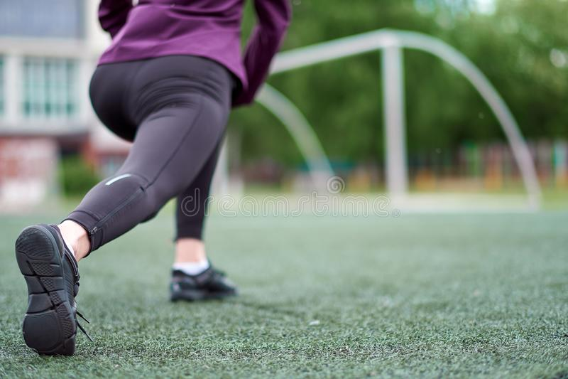 Étirage de femme Jeune séance d'entraînement femelle avant stage de formation de forme physique sur un terrain de football photographie stock