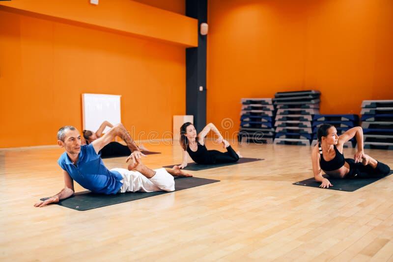 Étirage de l'exercice, groupe féminin de yoga dans l'action photo stock