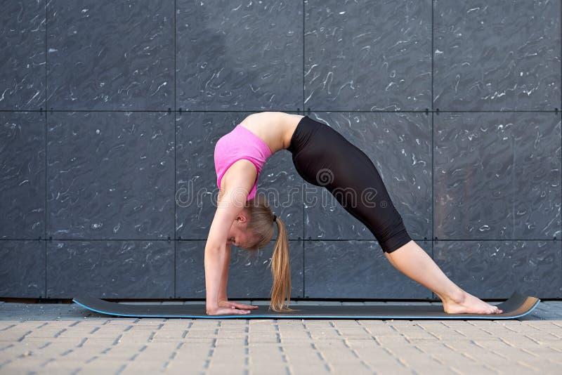 Étirage de la femme faisant le pont d'exercice Forme physique ou formation de gymnaste ou de danseur sur le fond gris de mur photos libres de droits