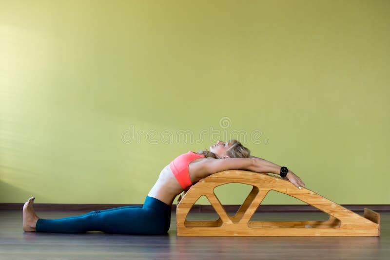 Étirage des exercices sur le banc de salto de yoga photographie stock libre de droits