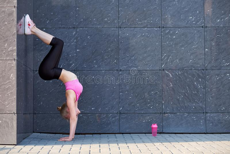 Étirage du femme forme physique ou gymnaste ou danseur faisant des exercices sur le fond uban de mur gris photographie stock libre de droits