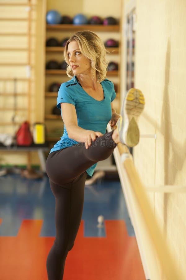 Étirage femelle dans la classe colorée de forme physique avec la balustrade photographie stock