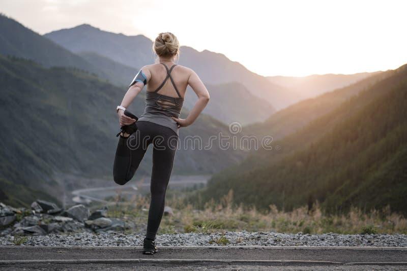 Étirage fonctionnant Athlète en haut de la montagne photo stock