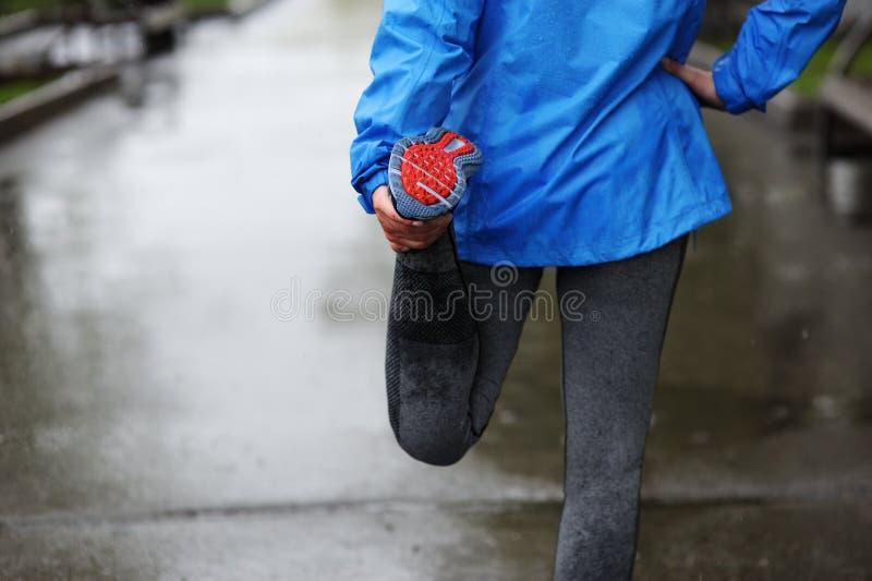 Étirage fonctionnant Plan rapproché des chaussures de course, femme étirant l image stock