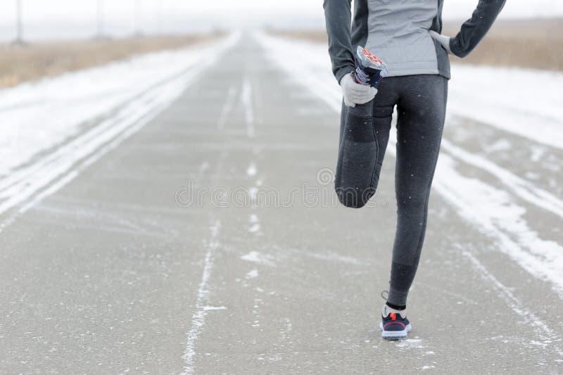 Étirant le fonctionnement - coureur de femme faisant des exercices Marath d'hiver image libre de droits