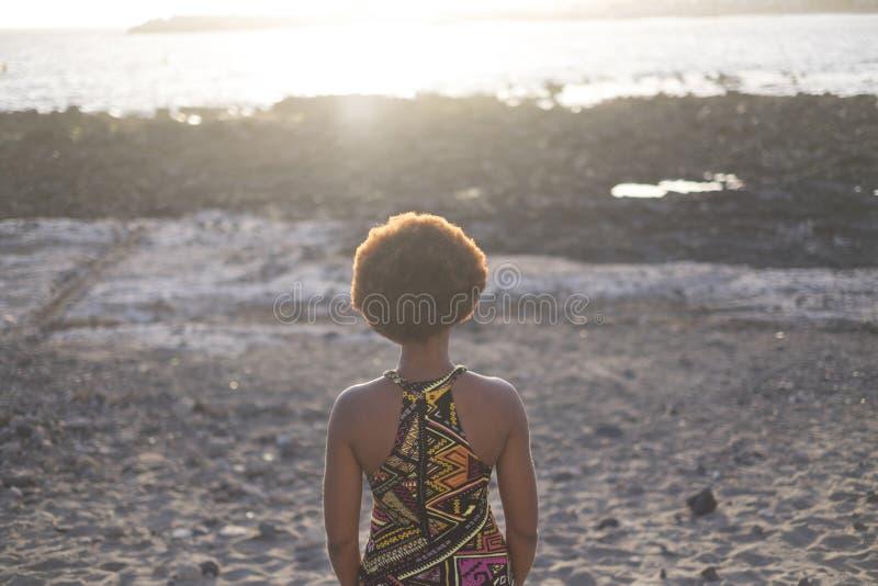 Étnico bonito só do africano da menina da raça preta visto da parte traseira que olha o por do sol e a luz sobre o mar nas férias foto de stock royalty free