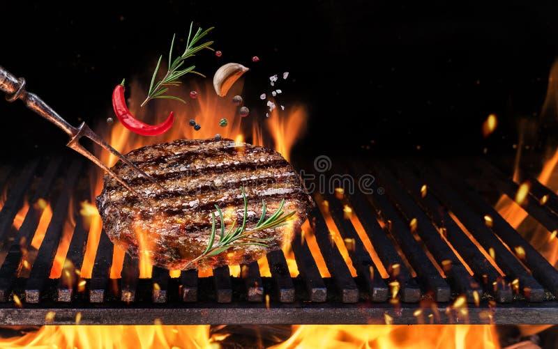 Étoffez la viande fraisée sur l'hamburger avec des épices volent au-dessus du feu flamboyant de barbecue de gril photo stock