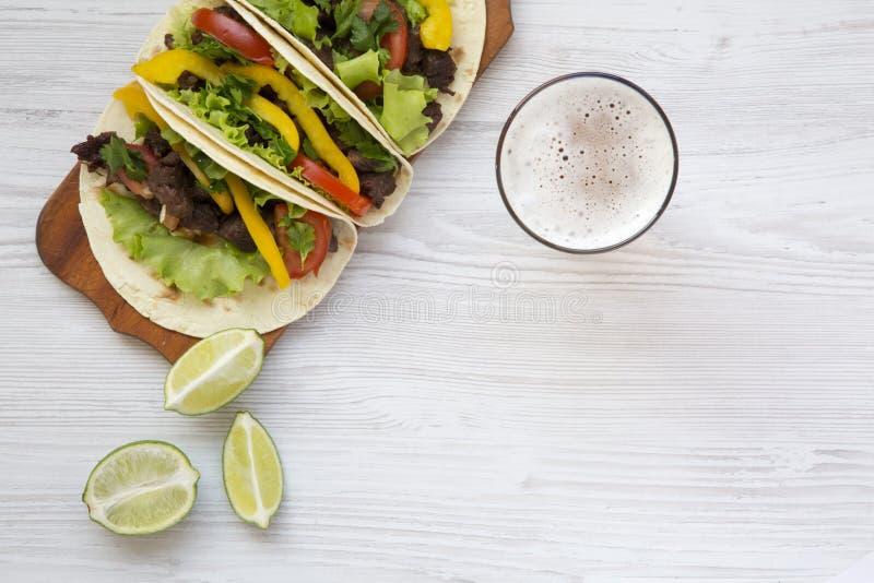 Étoffez le tacos avec de la salade, la tomate et la bière photos libres de droits