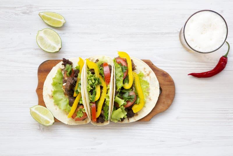 Étoffez le tacos avec de la salade, la tomate et la bière images stock