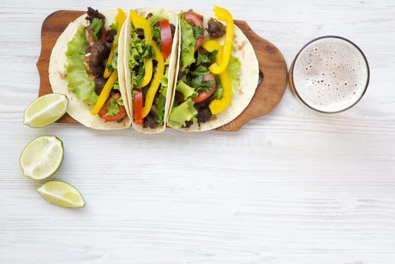 Étoffez le tacos avec de la salade, la tomate et la bière photographie stock libre de droits