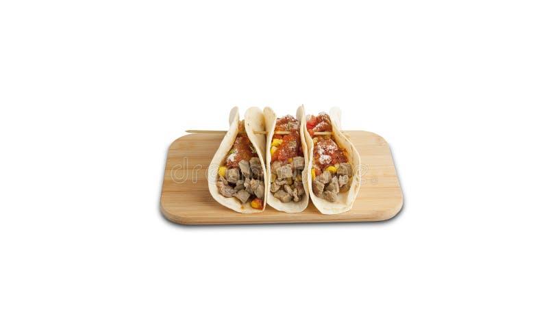 Étoffez le tacos sur un conseil en bois d'isolement sur un fond blanc image stock