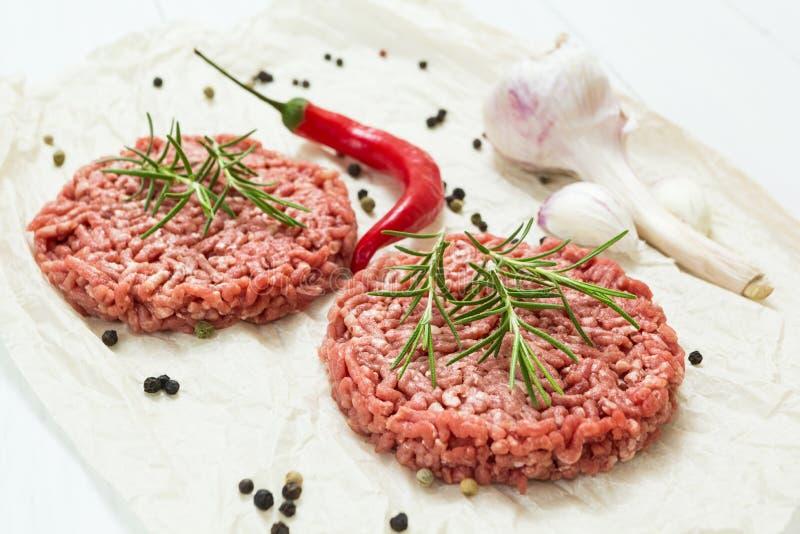 Étoffez les côtelettes crues avec des épices pour les aliments de préparation rapide sur un fond blanc Nourriture de rue photographie stock