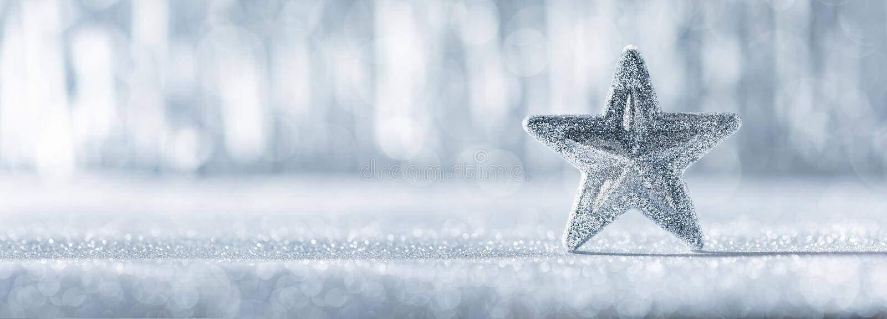 Étoile argentée brillante de Noël avec les lumières de Noël defocused à l'arrière-plan Drapeau de Noël photographie stock