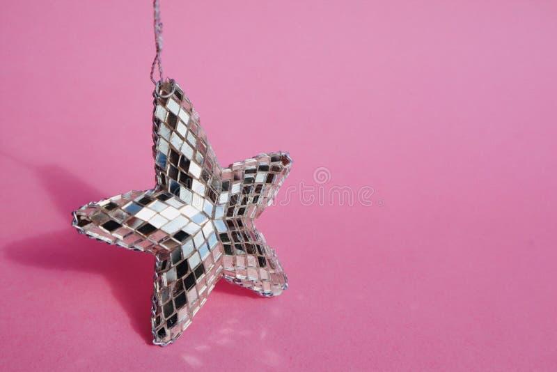 Étoile argentée lumineuse sur Pale Pink Background images libres de droits