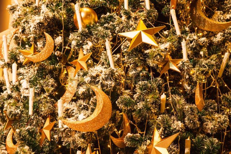 Étoile d'or, croissant de lune et fond éclatants accrochants de babioles de boule avec l'arbre de Noël neigeux décoré d'hiver dan image libre de droits