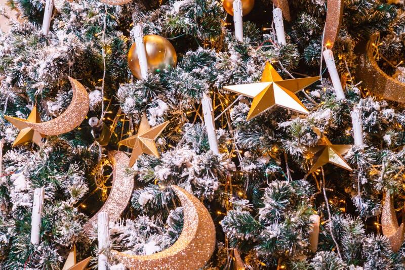 Étoile d'or, croissant de lune et fond éclatants accrochants de babioles de boule avec l'arbre de Noël neigeux décoré d'hiver dan photographie stock libre de droits