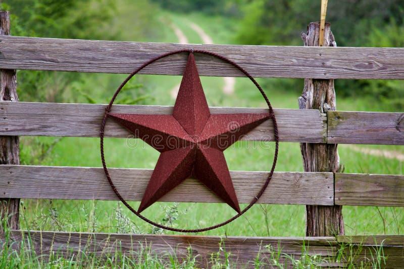 Étoile rustique du Texas sur la barrière en bois de côté de campagne, avec la route à la maison se dissolvant lentement à l'arriè images libres de droits
