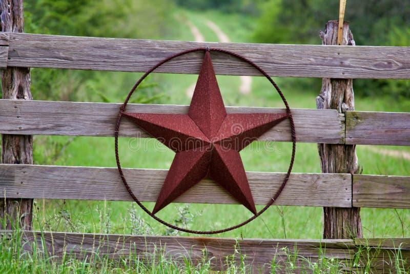 Étoile rustique du Texas sur la barrière en bois de côté de campagne, avec la route à la maison se dissolvant lentement à l'arriè photos stock