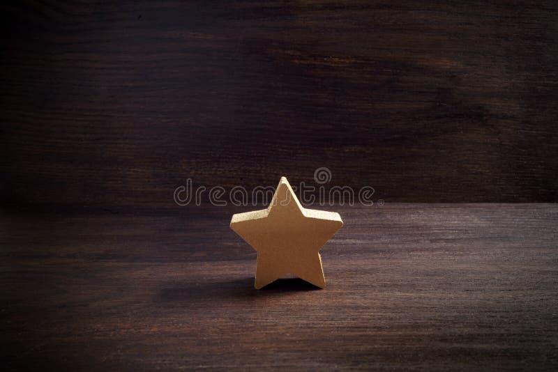 Étoiles d'or sur le fond en bois foncé, concept de évaluation supérieur photos libres de droits