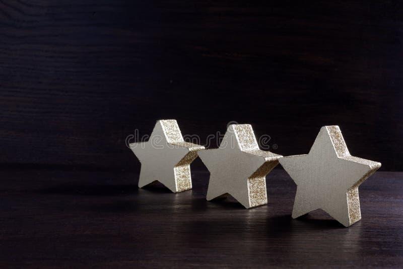 Étoiles d'or sur le fond en bois foncé, concept de évaluation supérieur photos stock