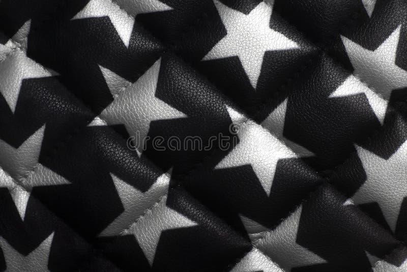 Étoiles de cuir blanc sur le fond en cuir noir photographie stock