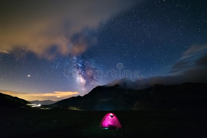 Étoiles de galaxie de manière laiteuse au-dessus des Alpes, de la tente lumineuse campante, de la planète de Mars et de Jupiter,  image libre de droits