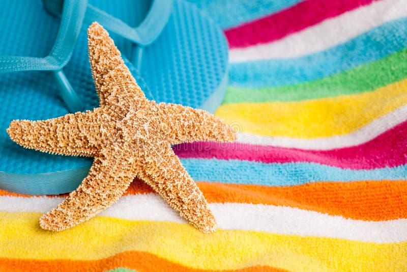 Étoiles de mer et bascules électroniques sur un essuie-main de plage images libres de droits