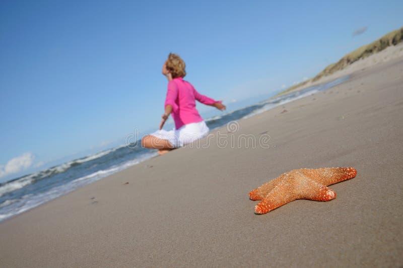 Étoiles de mer et femme tranquille sur la plage image stock